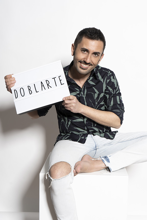 Jose Rua sentado con cartel de Doblarte