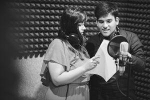 Un alumno y una alumna preparados para interpretar su take de canción. Ambos llevan cascos y están delante del micrófono.