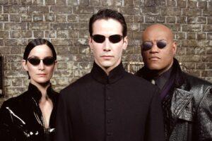 cartel de la pelicula matrix donde sus tres principales protagonistas miran a camara con gafas de sol negras