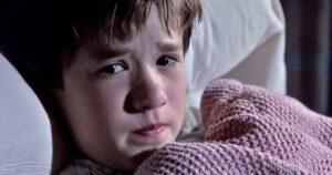 foto del niño protagonista de la pelicula el sexto sentido en una cama de hospital tapado con una manta rosa con cara de tristeza a punto de llorar