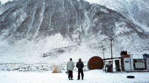 Dos hombres de espaldas observan una gran montaña nevada.